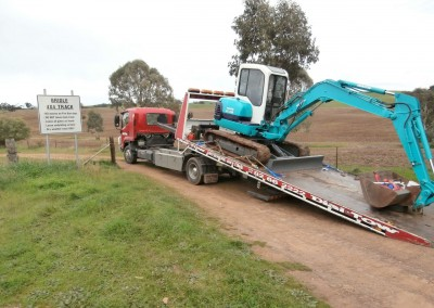 Mac Excavator towing the digger on a narrow 4x4 track