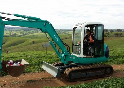 Dial-a-Tow's mini excavator towing agricultural machinery in the hilly terrains of South Australian country