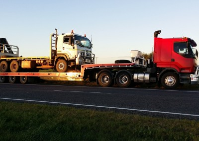 Towing a heavy vehicle across the borders on our low-bed tilt trucks