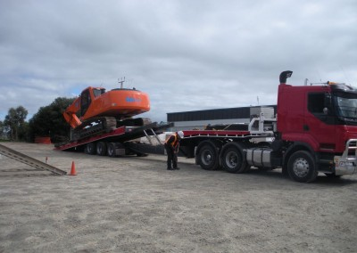 Our fleet's prized possession, the advanced Mac Excavator, towing an industrial machine for delivery on-site