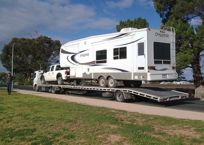 One of our low-bed semi trailers towing a broken down caravan along with the caravan towing vehicle