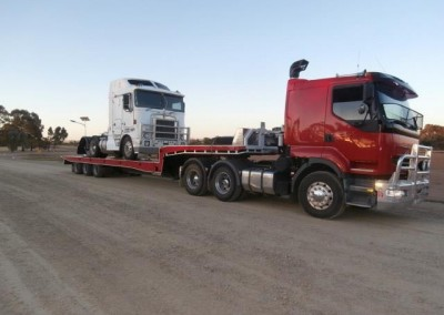 Towing a heavy vehicle part across the borders on our low-bed tilt trucks