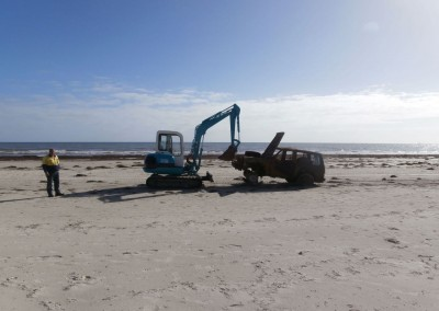 The front end loader dragging the recovery vehicle across the sand where a forklift's waiting to load it onto a tow truck