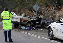 At an accident crash site with the crash car at rest in a horizontal position posing risk to oncoming traffic
