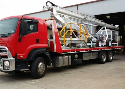 Dial-a-Tow tilt truck with heavy machinery loaded